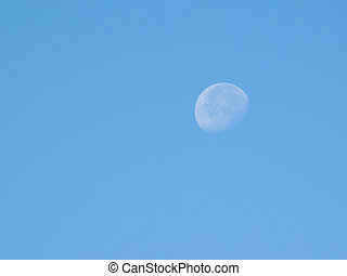 Waning gibbous moon over the blue sky