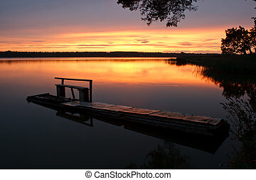 waning sunset - rickety wooden bridge on the pond in the...