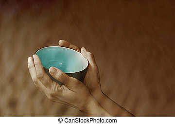 Hands holding up an empty bowl symbolizing want and poverty