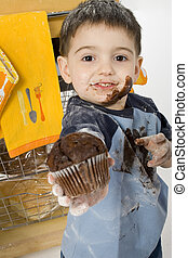Want One? - Three year old boy handing chocolate chip muffin...