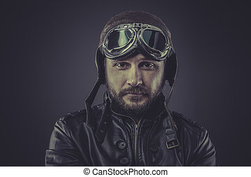war pilot dressed in vintage style leather cap and goggles