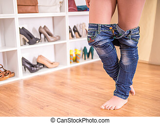 Wardrobe - Close-up of woman's legs is dressing jeans in the...