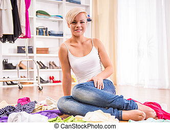 Wardrobe - Young woman is sitting on the floor with clothes...