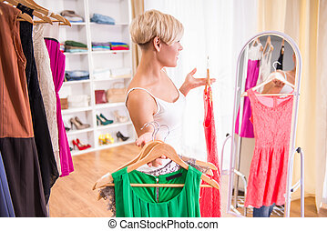 Wardrobe - Young beautiful woman is trying dresses in front...
