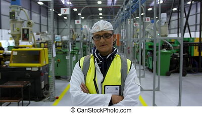 Warehouse female worker looking at camera with arms crossed...