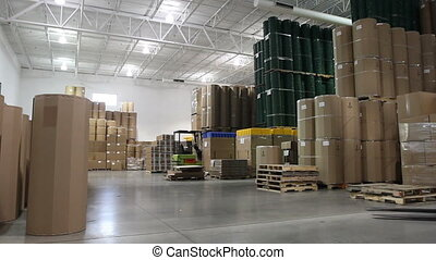 A forklift driver cruises through a large factory warehouse.