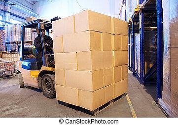 Worker driver of a forklift loader at warehouse loading cardboard boxes on pallet to shelves