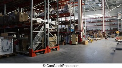 Warehouse full of goods with man in the background -...