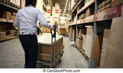 Warehouse. Man takes a box.