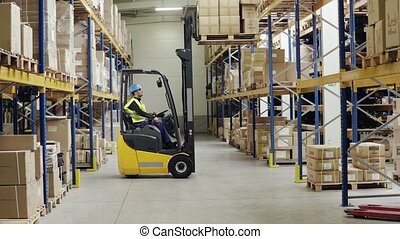 Young male worker lowering a pallet with boxes. Forklift driver working in a warehouse.