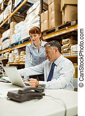 Warehouse management talking and looking at laptop