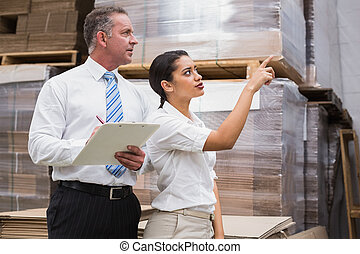 Warehouse manager and her boss checking inventory in a large...