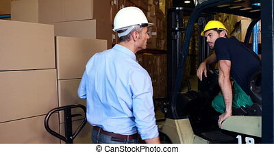 Warehouse manager working with foreman in forklift in a...
