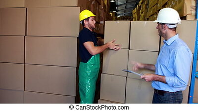 Warehouse manager working with foreman in a large warehouse