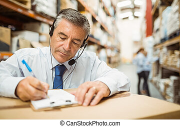 Warehouse manager writing on paper