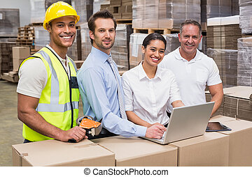 Warehouse managers and worker looking at camera in a large...