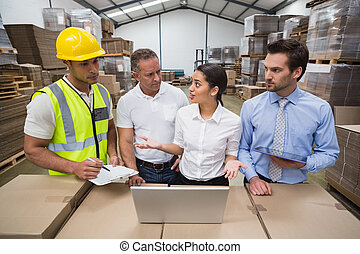 Warehouse managers and worker talking together