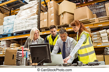 Warehouse managers and worker working on laptop in a large...