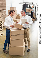 Warehouse managers checking their list in a large warehouse