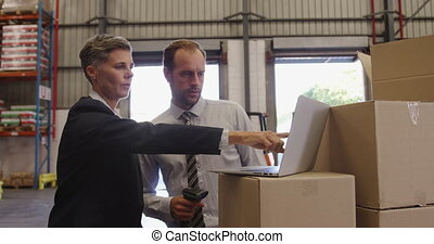 Warehouse managers working together in loading bay 4k - ...
