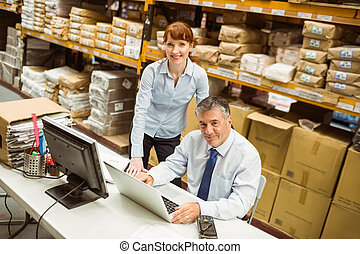 Warehouse managers working together on laptop