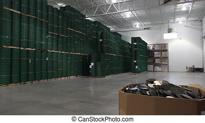The camera pans across a large warehouse filled with inventory.