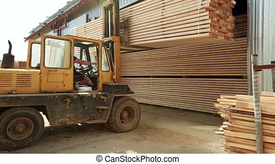 View on forklift loads boards into container - Warehouse...