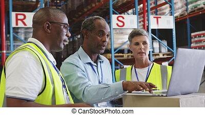 Warehouse staff meeting around a laptop 4k