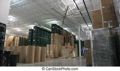 Warehouse Supervisor 1 - A businessman walks through a large...