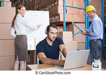 Warehouse team working together on shipment in a large...