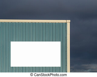 Warehouse with blank sign for message against stormy cloud background