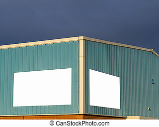 Warehouse with blank signs for message against stormy cloud background