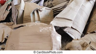 Large warehouse of waste paper in plant. Warehouse with recyclable materials at garbage processing factory. Huge pile of different paper pieces, rubbish, litter, trash, closeup view in motion.