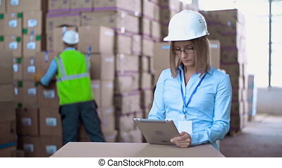 Warehouse Workday - Close up of woman in helmet browsing...