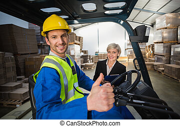 Warehouse worker and his manager smiling at camera