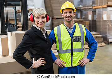 Warehouse worker and his manager with hands on hips