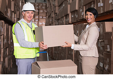 Warehouse worker and manager passing a box in a large...