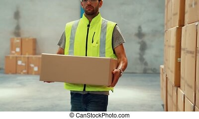 Warehouse worker carrying cardboard box in the warehouse . Packaging delivery and supply chain management concept .
