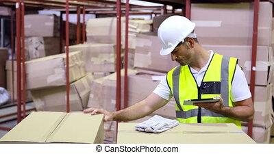 Warehouse worker checking boxes for shipping with tablet pc ...
