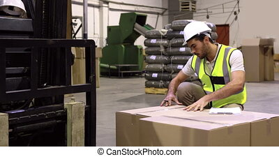 Warehouse worker checking cardboard boxes for shipping in a...
