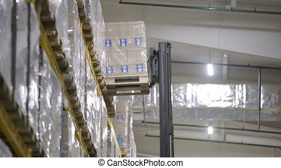 Warehouse worker driver loading cardboard boxes by forklift...