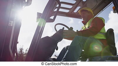 Warehouse worker driving forklift outside factory - Low ...