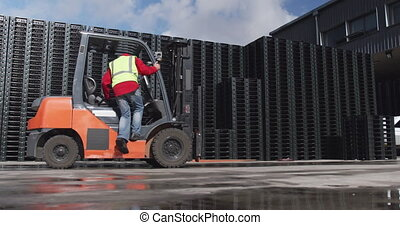 Side view of a mixed race male worker working at a busy factory warehouse, wearing high visibility vest, climbing into a forklift truck outside, in slow motion