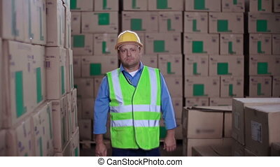 Warehouse Worker - Man in uniform approaching camera and...