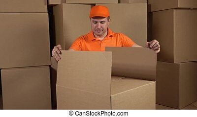 Warehouse worker in orange uniform unboxing big carton full of soft packaging material. Shockproof container. Multiple boxes background. Slow motion video