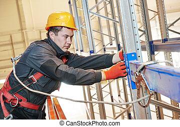 warehouse worker installing rack arrangement - One warehouse...