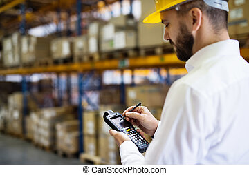 Warehouse worker or supervisor with barcode scanner. A...