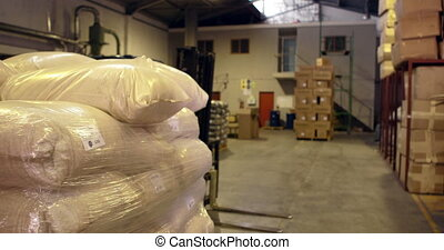 Warehouse worker packing up a palette in a warehouse