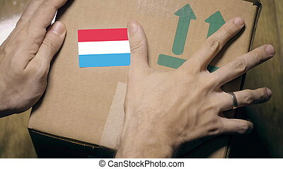 Warehouse worker places sticker with flag of Luxembourg on ...