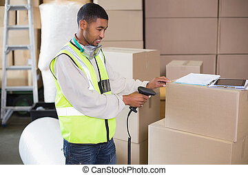 Warehouse worker scanning a box in a large warehouse